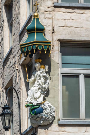 Antwerpen, Belgium: Closeup of white stone with golden crowns statue of Madonna with child on corner of Eiermarkt and Suderman Straat. Gray facade with window and streetlantern.