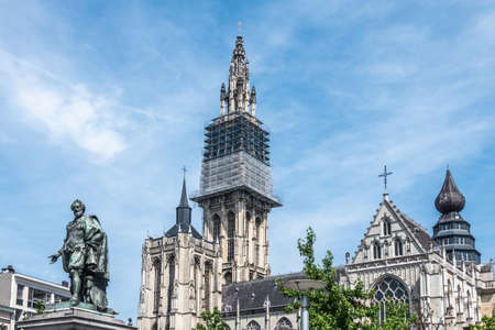 Antwerpen, Belgium: Bronze Peter Paul Rubens statue fronts towers and nave of Notre Dame, Onze-Lieve-Vrouw, cathedral against light blue sky. Some green foliage.