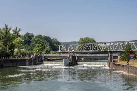 Dinant, Belgien: Metalleisenbahnbrücke überspannt die Maas mit künstlicher Stromschnelle vor der Schleuse unter hellblauem Himmel. Grünes Laub.