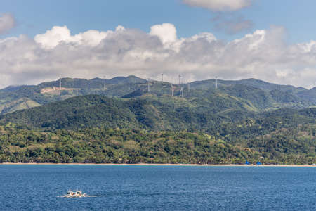 Caticlan, Malay, Philippines - March 4, 2019: Green mountain range with windmills dispersed under blue sky with thick gray cloudscape. Blue sea wth small outrigger boat. Imagens