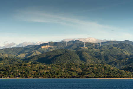 Caticlan, Malay, Philippines - March 4, 2019: Green mountain range with windmills dispersed under blue sky with thick gray cloudscape. Dark blue sea.