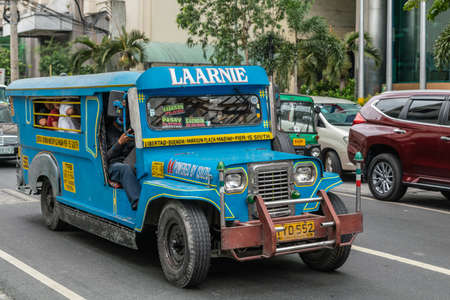 Manila, Philippines - March 5, 2019: Sky blue long Isuzu Jeep Public Transport called Laarnie in street. Side and front view. People inside. Green foliage. Other car and gray buildings.