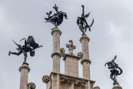 Gent, Flanders, Belgium -  June 21, 2019: Closeup of Dark Bronze Four dancers statue on beige gable top of Metselaarshuis, Masons Guild House against light blue sky. Redactioneel