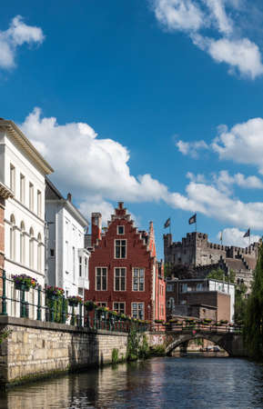 Gent, Flanders, Belgium -  June 21, 2019: Narrow Lieve River leads along old bourgeois mansions to Gravensteen Castle under blue sky with white clouds. Bluish water. Flowers on quays. Editöryel
