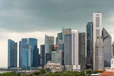 Singapore - March 20, 2019: Line of financial district skyscrapers from the bay to Victoria Theatre clock tower under dark gray cloudscape, with green foliage of Esplanade Park in front.