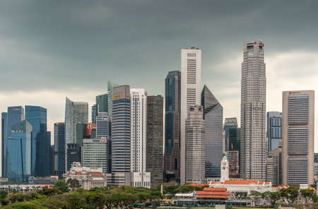 Singapore - March 20, 2019: Line of financial district skyscrapers from DBS to OCBC bank buildings under dark gray cloudscape. Victoria theatre and Cricket Club in front with green foliage and red roofs.