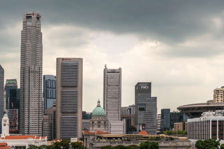 Singapore - March 20, 2019: Line of financial district skyscrapers from J.P.Morgan to Supreme Court buildings under dark gray cloudscape. Victoria theatre and Green dome of National Gallery dome.