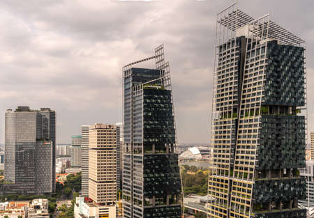 Singapore - March 20, 2019: Combination shot of black Facebook and Rabo Bank skyscrapers, Andaz and Mastercard to the left, and JW Marriott towers to the right  under heavy sky.
