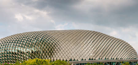 Singapore - March 20, 2019: Closeup of One Esplanade Theatres dome under heavy cloudscape. Some green folliage.