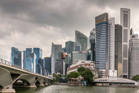 Singapore - March 20, 2019: White antique Anderson Bridge, modern Esplanade bridge and a few towers of financial district under heavy cloudscape. Some green foliage.