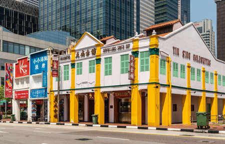 Singapore - March 22, 2019: Chinatown. Yin Sing Goldsmiths and Jewellers on South Bridge Road is large white and yellow corner building. Skyscrapers behind, and other retailers as neighbors. Zdjęcie Seryjne - 136349883