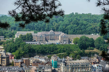 Dinant, Belgium - June 26, 2019: Seen from Citadelle. Large building is College Notre Dame de Bellevue, school system from primary to high school. Forests in back. Light blue sky. 新聞圖片