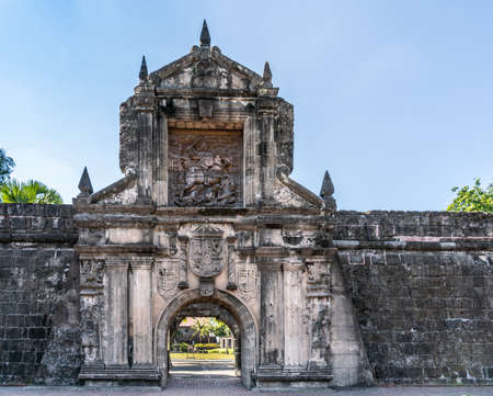 Manila, Philippines - March 5, 2019: Fort Santiago. Monumental main gate into the fortress with images of Saint James on his horse, and the coat of arms of King of Spain, all in beige stones covered in black mold. Editorial