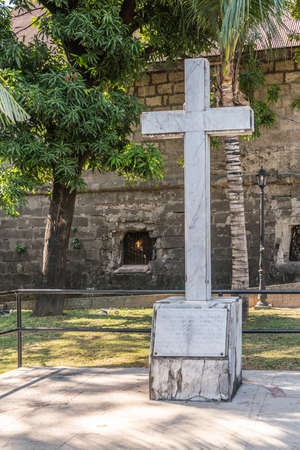 Manila, Philippines - March 5, 2019: Fort Santiago. White marble cross as memorial for execution by Japan of over 600 Filipino and American prisoners at the fortress at end of February 1945.