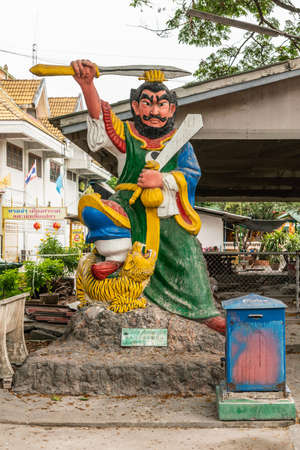 Bang Saen, Thailand - March 16, 2019: Wang Saensuk Buddhist Monastery. Tall colorful statue of man defeating a tiger which he holds under his foot, while holding two sword and a bag of money. Green fo