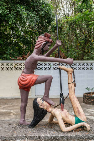 Bang Saen, Thailand - March 16, 2019: Garden of Hell in Wang Saensuk Buddhist Monastery. Scene wherein devil spears lying on the ground woman while holding her chain. Zdjęcie Seryjne