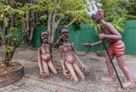 Bang Saen, Thailand - March 16, 2019: Garden of Hell in Wang Saensuk Buddhist Monastery. Scene wherein devil with trident threatens chained couple. Green foliage.