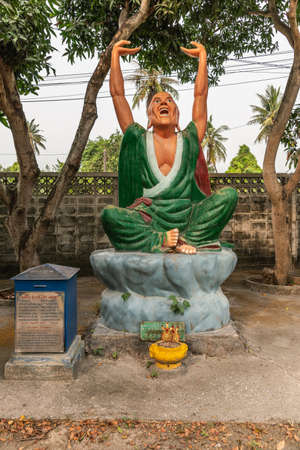 Bang Saen, Thailand - March 16, 2019: Wang Saensuk Buddhist Monastery. Colorful statue of Pra Na Kia Sai Na, the second Saint  in green dress and hands up under silver sky and green foliage. Banco de Imagens