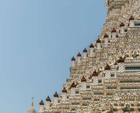 Bangkok city, Thailand - March 17, 2019: Stairway like architecture of flanks of Temple of Dawn against blue sky. Porcelain and faience decoration all the way.