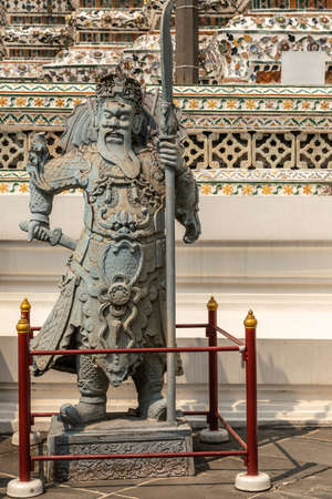 Bangkok city, Thailand - March 17, 2019: Chinese style warrior statue at bottom of Temple of Dawn, with porcelain faience decoration in back.