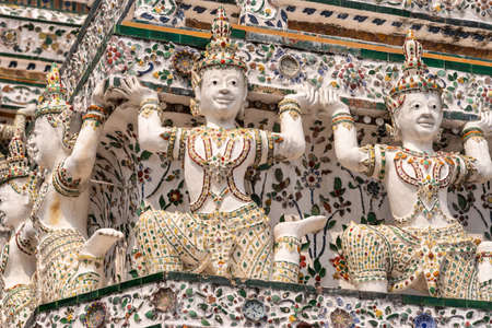 Bangkok city, Thailand - March 17, 2019: Closeup of detail of corner of Temple of Dawn, with its porcelain faience surface, shows four statues of humans pretending to hold up the rest of the temple.
