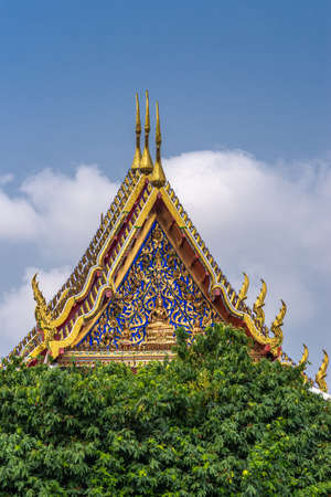 Bangkok city, Thailand - March 17, 2019: Three golden gables with intense blue decoration towering over green foliage at Temple of Dawn against blue sky. 版權商用圖片