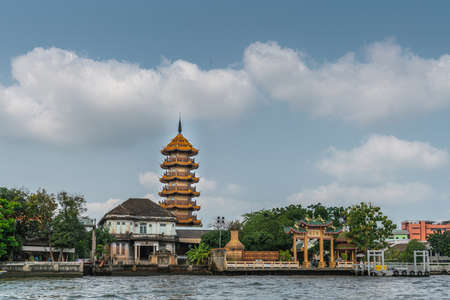 Bangkok city, Thailand - March 17, 2019: Wide view Chao Phraya River. Chee Chin Khor temple and red roofs Pagoda against blue cloudscape with green foliage in front. Chinese style gate at docking platform. Editorial
