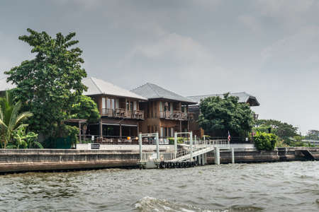 Bangkok city, Thailand - March 17, 2019: Bangkok Noi Canal. Group of two-story brown wooden mansions with their own boat dock under cloudscape. Green foliage along the quay.