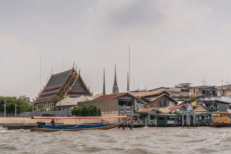 Bangkok city, Thailand - March 17, 2019: Chao Phraya River. Market and poor housing as neighbors of National Grand Palace under silver cloudscape. Small boat in front. Spires and special architecture.