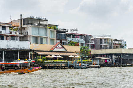 Bangkok city, Thailand - March 17, 2019: Chao Phraya River. Famous Sala Ratanakosin restaurant and bar with its business neighbors. Small ferry passes in front under silver-blue cloudscape. Zdjęcie Seryjne - 136350133