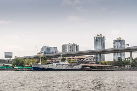 Bangkok city, Thailand - March 17, 2019: Chao Phraya River. White-black restaurant ship Vanvarang docked near Rama III Bridge over river. Supalai Casa Rive Fonte residential towers in back.