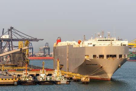 Laem Chabang seaport, Thailand - March 17, 2019: Front view of tall large gray vehicles transport ship, American Highway, Panama flagged, under sunset light. Three tugboats and cranes. Éditoriale