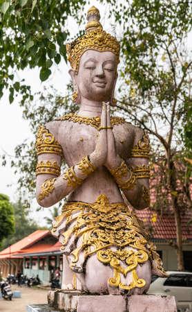Ko Samui Island, Thailand - March 18, 2019: Wat Khunatam Buddhist Temple and monastery. Pinkish Bodhisattva statue with golden ornaments under green foliage and silver sky. Stockfoto