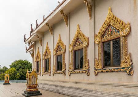 Ko Samui Island, Thailand - March 18, 2019: Wat Khunatam Buddhist Temple and monastery. Windows set in elaborately decorated golden frames with gemstones set in beige walls. Stockfoto