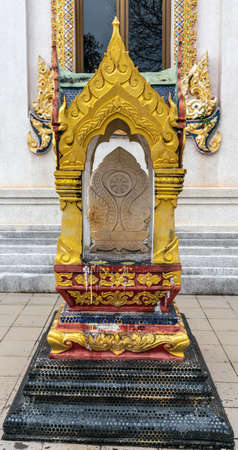 Ko Samui Island, Thailand - March 18, 2019: Wat Khunatam Buddhist Temple and monastery. Offer platform and golden monument with chakra symbol and damaged by flames. Window of sanctuary in back.