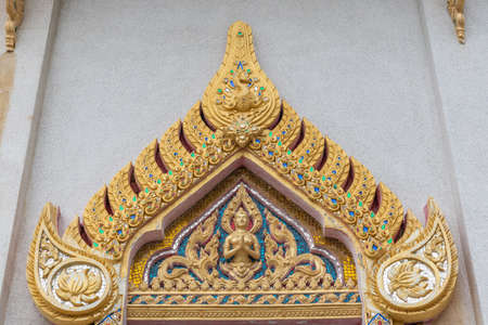 Ko Samui Island, Thailand - March 18, 2019: Wat Khunatam Buddhist Temple and monastery. Golden triangular decoration filled with colored gemstones above window of temple building.