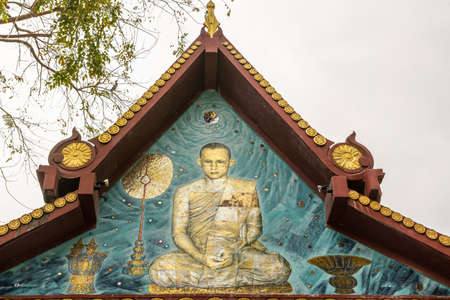 Ko Samui Island, Thailand - March 18, 2019: Wat Khunatam Buddhist Temple and monastery. Painted on gable, closeup image of monk Luang Por Deeng, saint of the temple. Silver sky and green foliage. Stockfoto - 133201835