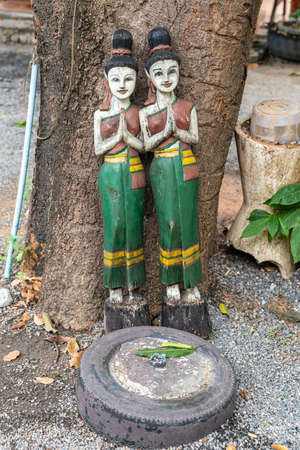 Ko Samui Island, Thailand - March 18, 2019: Wat Khunatam Buddhist Temple and monastery. Sculpture of two similarly dressed women against tree trunk with offering plateau captured in car tire.