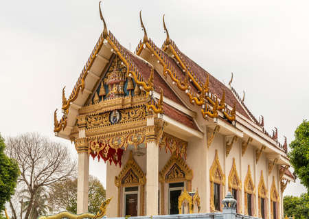 Ko Samui Island, Thailand - March 18, 2019: Wat Khunatam Buddhist Temple and monastery. Front, side and roof of royal shrine against silver sky. Abundance of golden decorations with snakes.