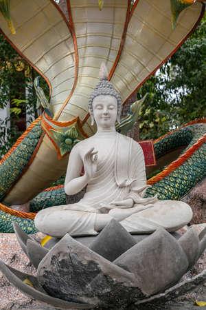 Ko Samui Island, Thailand - March 18, 2019: Wat Khunatam Buddhist Temple and monastery. Closeup, White Bodhisattva statue sitting on lotus with colorful snakes above under ficus religiosa tree.
