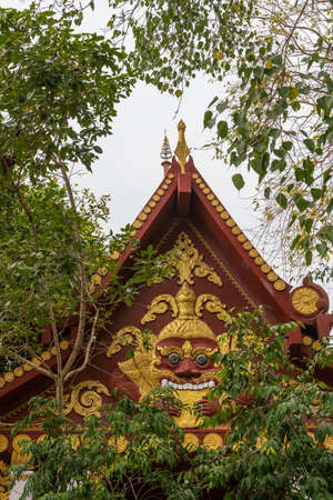 Ko Samui Island, Thailand - March 18, 2019: Wat Khunatam Buddhist Temple and monastery. Maroon gable with golden decorations of scary face, framed by green foliage against silver sky.