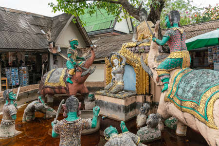 Ko Samui Island, Thailand - March 18, 2019: Wat Phra Yai Buddhist Temple on Ko Phan. Complex statue group of Buddha above scene from hell with devils on elephants and sinner in the pit.