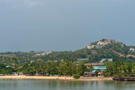 Ko Samui Island, Thailand - March 18, 2019: Beach adjacent to Wat Phra Yai Buddhist Temple on Ko Phan. Green hills with plenty of buildings, yellow sand and beach houses, a couple canoes and blue sky.