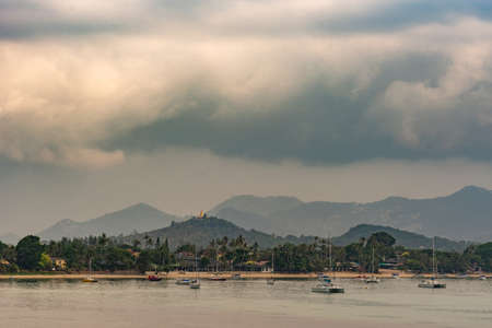 Ko Samui Island, Thailand - March 18, 2019: Off Wat Phra Yai Buddhist Temple on Ko Phan. Green mountains behind sandy beach wtih sail boats and resorts under heavy cloudscape. Golden sprang on hill top.