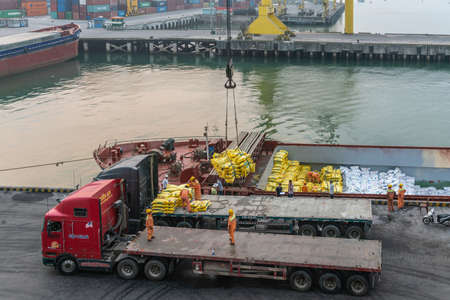 Da Nang, Vietnam - March 10, 2019: Tien Sa Port in Da Nang Bay. Crane takes loose yellow and white bags in a sling out of ship and transfers to flat bed truck, to be restacked manually. Redakční