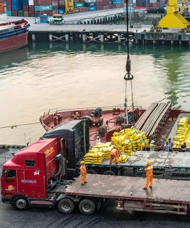Da Nang, Vietnam - March 10, 2019: Tien Sa Port in Da Nang Bay. Closeup: crane deposits loose yellow bags in a sling, out of ship, and transfers to flat bed truck, to be restacked manually. Redakční
