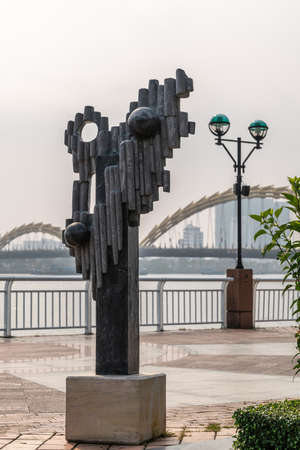 Da Nang, Vietnam - March 10, 2019: Han River Boardwalk art exhibition. Black marble non-figurative statue with tall buildings and bows of dragon bridge in back.