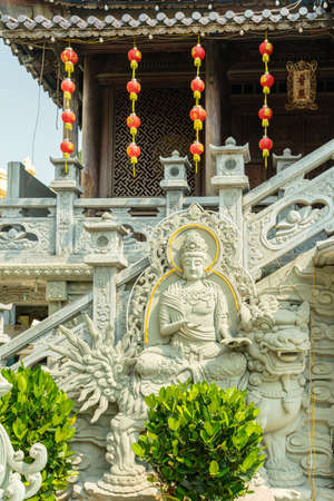 Da Nang, Vietnam - March 10, 2019: Chua An Long Chinese Buddhist Temple. Gray stone Bodhisattva fresco at bottom of stairway leading to brown pagode proper. Red balloon lanterns and green plants in front. Stockfoto