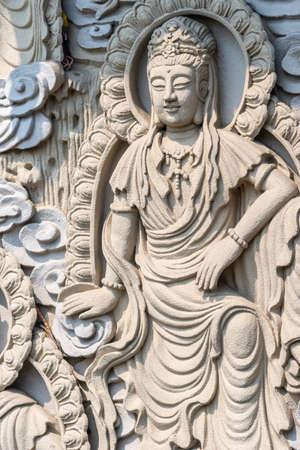 Da Nang, Vietnam - March 10, 2019: Chua An Long Chinese Buddhist Temple. Closeup of Gray stone happy standing Bodhisattva fresco as backdrop for Guan Yin statue, not in picture. Stockfoto