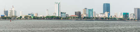 Da Nang, Vietnam - March 10, 2019: Panorama shot of downtown from accross Han River with skyscrapers and other buildings. Green foliage band separates water from stones. Editorial